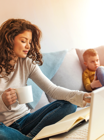 A young mother looking  through her Express Scripts Canada health benefits package while sitting on the couch with her son playing in the background