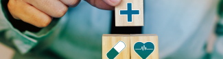 Person placing wooden block with cross icon on top of two other wooden blocks with a pill and heart symbol on each